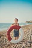 男孩坐在镶边衬衣有一海洋lifebuoy的, liferound的海滩 男孩坐在一个美丽的海滩的沙子 Beautif 库存照片