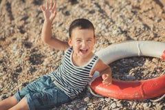 男孩坐在镶边衬衣有一海洋lifebuoy的, liferound的海滩 男孩坐在一个美丽的海滩的沙子 Beautif 免版税图库摄影