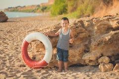 男孩坐在镶边衬衣有一海洋lifebuoy的, liferound的海滩 男孩坐在一个美丽的海滩的沙子 Beautif 免版税库存图片