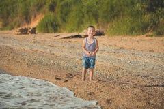 男孩坐在镶边衬衣有一海洋lifebuoy的, liferound的海滩 男孩坐在一个美丽的海滩的沙子 Beautif 图库摄影