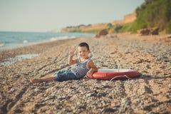 男孩坐在镶边衬衣有一海洋lifebuoy的, liferound的海滩 男孩坐在一个美丽的海滩的沙子 Beautif 库存图片