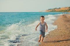 男孩坐在镶边衬衣有一海洋lifebuoy的, liferound的海滩 男孩坐在一个美丽的海滩的沙子 Beautif 免版税库存照片