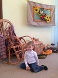 男孩坐地板在摇椅旁边 免版税库存照片