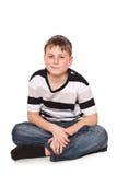 男孩坐地板 免版税图库摄影