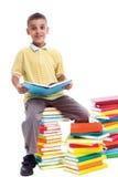 男孩坐堆书和学会 免版税库存照片