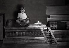 男孩坐大书 一个木楼梯导致堆书 免版税库存照片