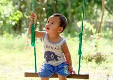 男孩坐摇篮 图库摄影