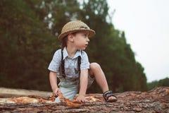 男孩坐日志 图库摄影