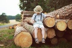 男孩坐日志 免版税库存图片