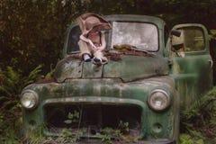 男孩坐残破的卡车 免版税库存图片