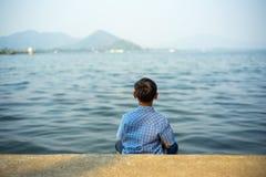 男孩坐海滨俯视的视图在轰隆Phra水库chonburi泰国 免版税库存照片