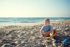 男孩坐海滩 库存图片