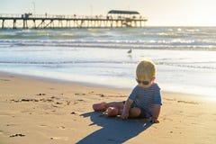 男孩坐海滩 库存照片