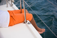 年轻男孩坐游艇边 免版税库存照片