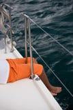 年轻男孩坐游艇边 库存照片