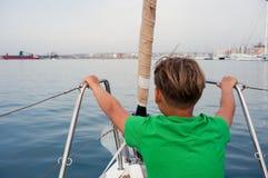 男孩坐游艇鼻子 免版税图库摄影