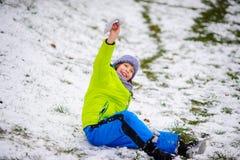 男孩坐用第一雪有一点报道的地面 库存照片