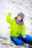 男孩坐用第一雪有一点报道的地面 免版税库存图片