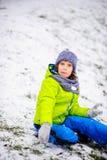 男孩坐用第一雪有一点报道的地面 免版税库存照片