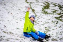 男孩坐用第一雪有一点报道的地面 库存图片