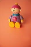 男孩坐的微笑的玩具 免版税库存图片