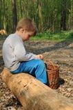 男孩坐的树干 免版税库存图片