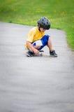 男孩坐的滑板 免版税图库摄影