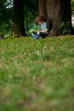 男孩坐盘腿在一棵大树附近在公园 免版税库存照片
