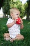男孩坐草在公园,使用与球 图库摄影