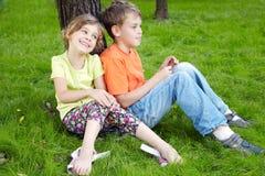 男孩坐草,他的姐妹在他旁边坐 库存图片