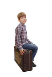 男孩坐葡萄酒手提箱 库存照片