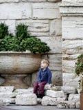 男孩坐装饰石头在一朵大花附近的滑稽的孩子是 图库摄影