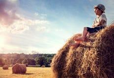 男孩坐观看日落的干草堆 免版税库存照片