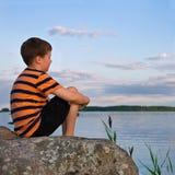男孩坐观看海边风景的一个大岩石 库存照片