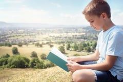男孩坐读一本书的小山在草甸 免版税库存图片