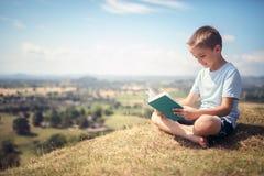 男孩坐读一本书的小山在草甸 库存图片