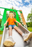 男孩坐金属滑道并且准备滑 免版税库存照片