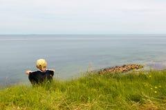 男孩坐陡坡的te边缘,高obove海 免版税库存图片