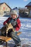 男孩坐雪撬 免版税库存图片
