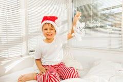 男孩坐他的在睡衣和圣诞老人帽子的坏 库存图片