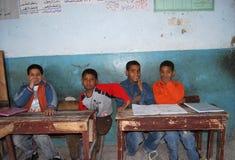 男孩坐他们的盘在类的一个教训在学校在埃及 免版税库存照片