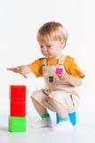 男孩坐他的腰臀部分并且演奏立方体 库存照片