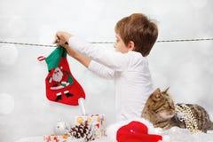 男孩垂悬圣诞老人的袜子 库存照片