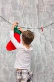 男孩垂悬圣诞老人的袜子 库存图片