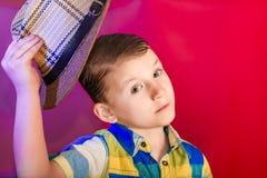 男孩培养在他的头的一个草帽在问候和友善的标志 免版税库存照片