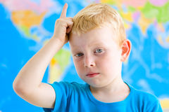 男孩培养他的在地理教训的手 免版税库存照片
