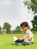男孩外部学习的年轻人 免版税库存照片