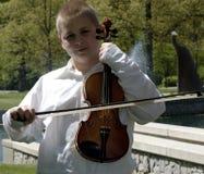 男孩外部常设中提琴 免版税库存图片