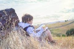 男孩外面阅读书 库存照片