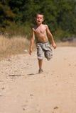 男孩多灰尘的路运行中 免版税库存图片